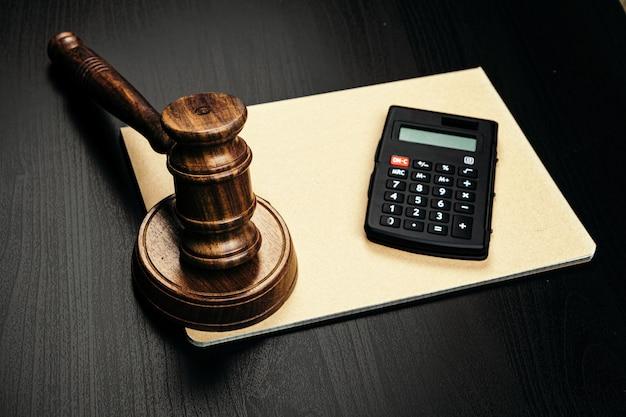 Mazo y calculadora de madera del juez en la mesa