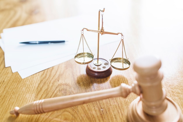 Mazo; escala de justicia; pluma y papeles en blanco en el escritorio de madera