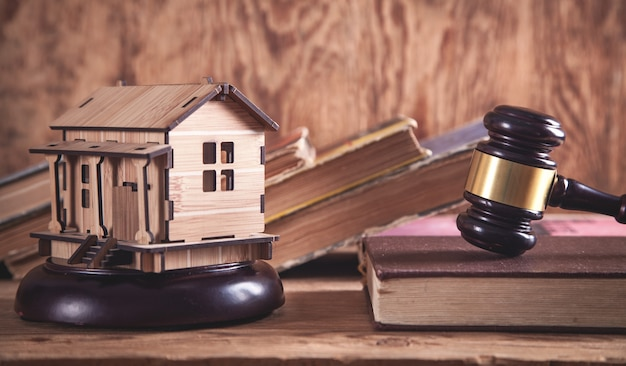 Mazo de juez con un modelo de casa de madera.