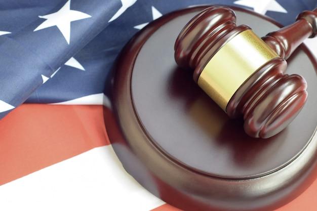 Mazo de justicia en la bandera de estados unidos en una sala del tribunal durante un juicio judicial