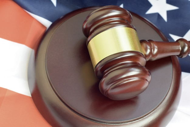 Mazo de justicia sobre la bandera de los estados unidos en una sala del tribunal durante un juicio judicial