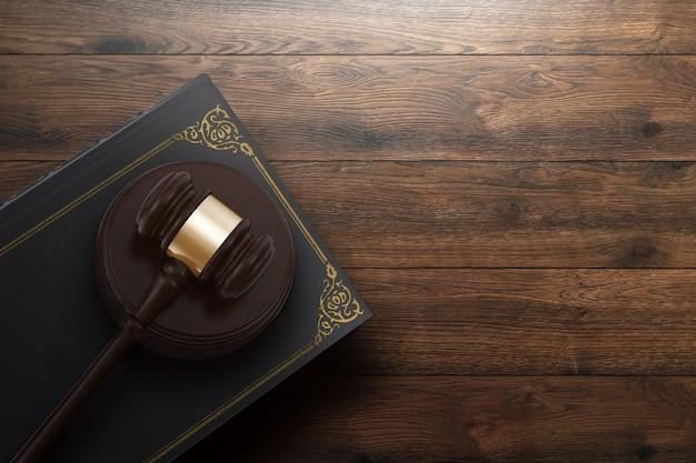 Mazo y libro del juez sobre fondo de madera.