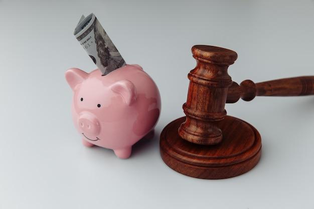 Mazo de madera y hucha rosa con billete de un dólar