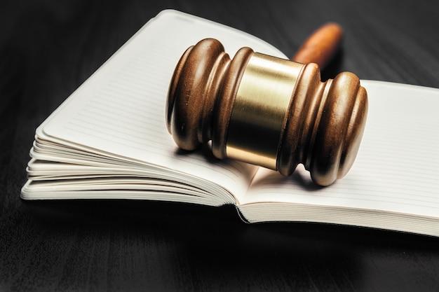 Mazo de madera marrón del juez en el fondo del libro abierto