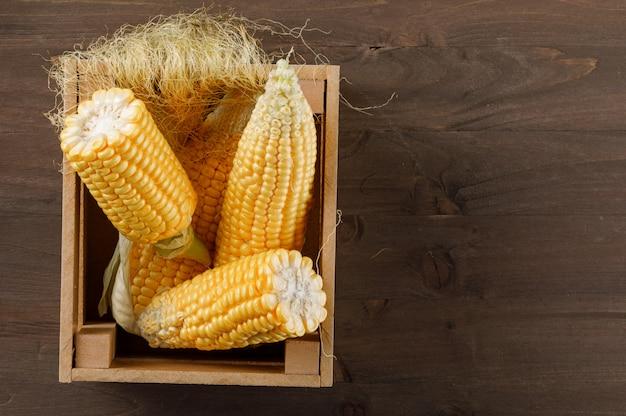 Mazorcas de maíz en una caja de madera con rodajas vista superior sobre una mesa de madera oscura