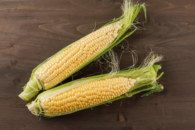 Mazorcas de maíz maduras en una mesa de madera oscura. aplanada