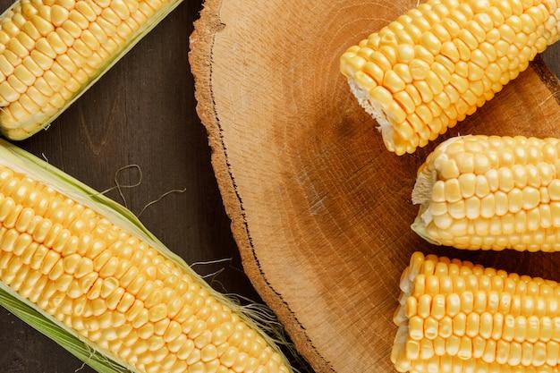 Mazorcas de maíz en una pieza de madera sobre una mesa de madera. aplanada