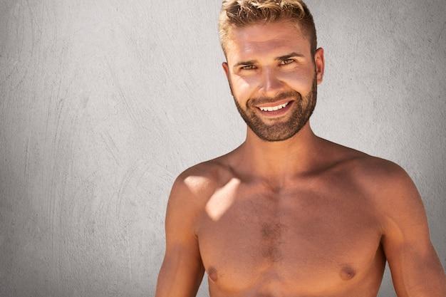 Me alegro de un hombre en topless con un peinado y una cerda de moda que tiene una fuerte construcción del cuerpo posando contra la pared gris con expresión feliz. modelo masculino atractivo con muscules aislado en muro de hormigón