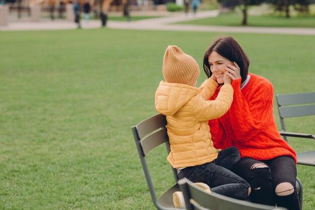 Me alegro de que la madre y la hija se sientan en chiar al aire libre, tienen expresiones positivas