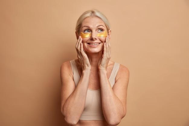 Me alegro de que la mujer rubia de mediana edad toca la cara aplica suavemente parches de belleza de colágeno debajo de los ojos tiene una expresión de ensueño