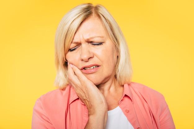 ¡me duelen los dientes! hermosa mujer senior rubia trastornada con dolor de muelas severo aislado en estudio sostiene su mejilla