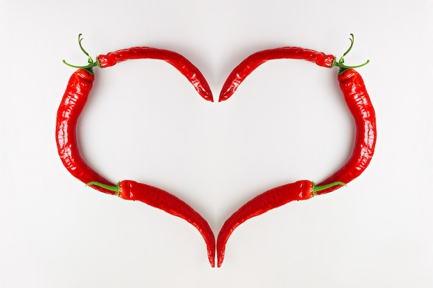 Me encanta el ají rojo, en forma de corazón en la mesa de madera blanca, vista superior