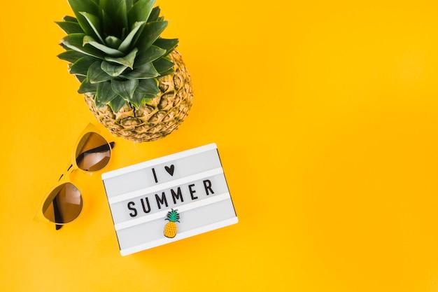 Me encanta la caja de luz de verano; gafas de sol y piña sobre fondo amarillo