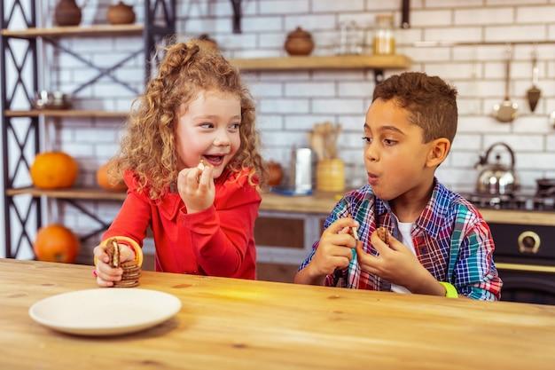 Me encanta. muchacho emocional sentado en la mesa mientras mira las galletas de su amigo