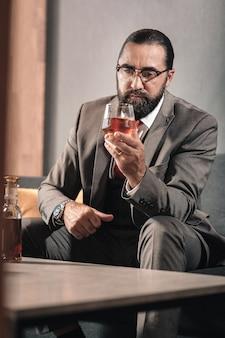 Me siento fatal. hombre moreno barbudo bebiendo whisky mientras se siente mal después de dejar a su familia