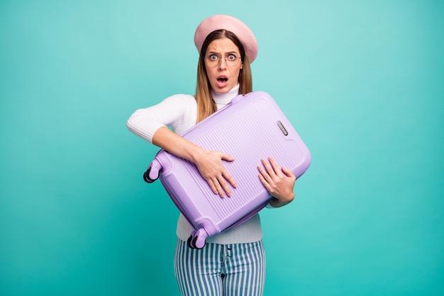 ¿me estás tomando el pelo? foto de señora bonita mantenga maleta violeta registro en el aeropuerto con sobrepeso necesita pagar dinero desgaste especificaciones boina rosa pantalones vaqueros de cuello alto blanco aislado fondo de color verde azulado