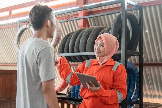 Mecánica asiática velada utiliza una tableta digital mientras charla con consumidores masculinos de pie con una rejilla para neumáticos