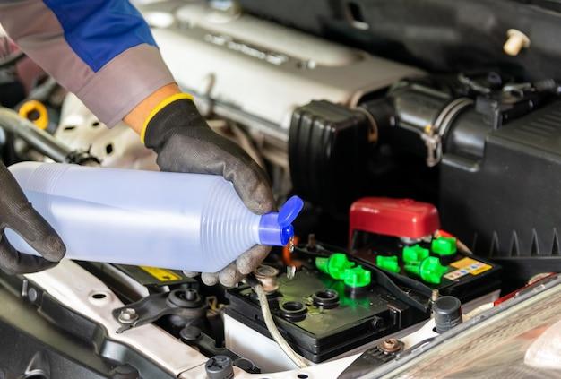 El mecánico agrega agua destilada y revisa la batería del auto.