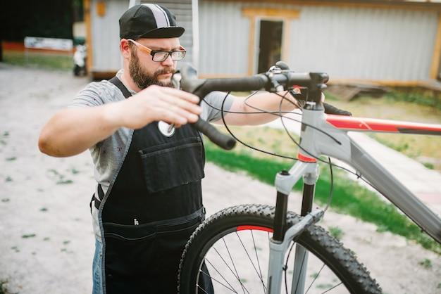 El mecánico ajusta el manillar y los frenos de la bicicleta.