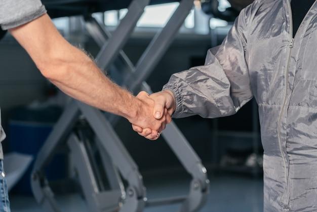 Mecánico un apretón de manos con el propietario del coche en el concepto de servicios de auto de taller garaje coche