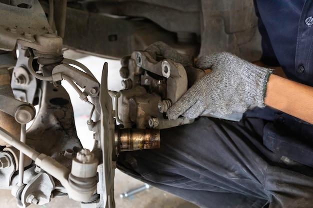 El mecánico está arreglando las pastillas de freno en el garaje