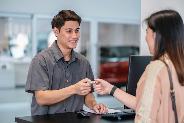 Mecánico asiático que recibe la llave automática del auto para verificar en el centro de servicio de mantenimiento