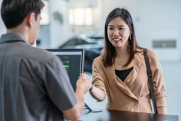 Mecánico asiático que recibe la llave automática del automóvil para verificar el servicio de mantenimiento en la sala de exposición