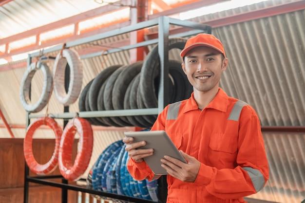 Mecánico asiático sonriente en wearpack usando una almohadilla mientras está en el taller con una rejilla para neumáticos detrás