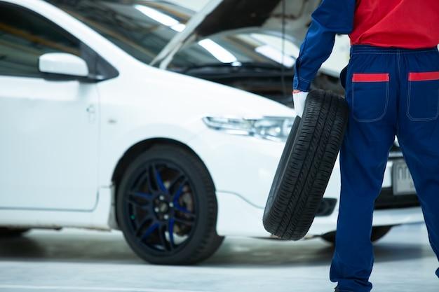 Mecánico asiático en uniforme de pie sosteniendo un neumático de automóvil está cambiando los neumáticos de las ruedas mientras trabaja en el centro de reparación de automóviles