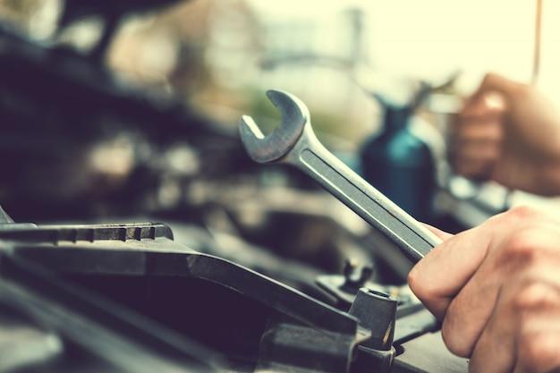 Mecánico automotriz trabajando en garaje técnico manos del mecánico automotriz trabajando en reparación automotriz servicio y mantenimiento de chequeo de automóviles.