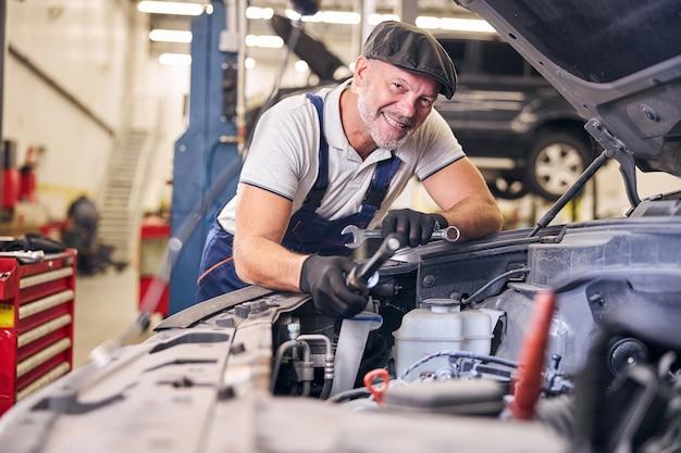 Mecánico de automóviles alegre que trabaja en la estación de servicio de reparación de automóviles