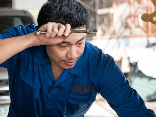 Mecánico de automóviles asiático joven en uniforme que sostiene la llave y que limpia sudor.