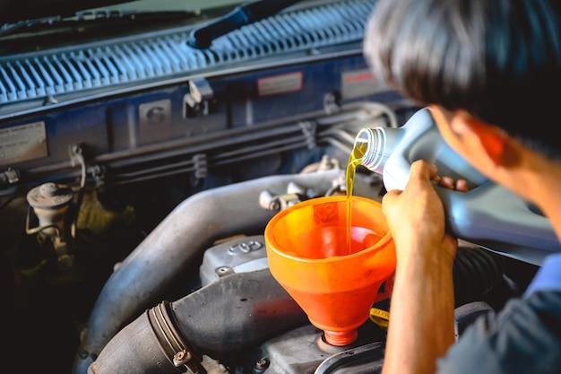 Mecánico de automóviles asiático que trabaja en un taller de reparación de automóviles vierta aceite para el cambio de aceite en el garaje para los clientes que reparan automóviles y cambian el aceite.