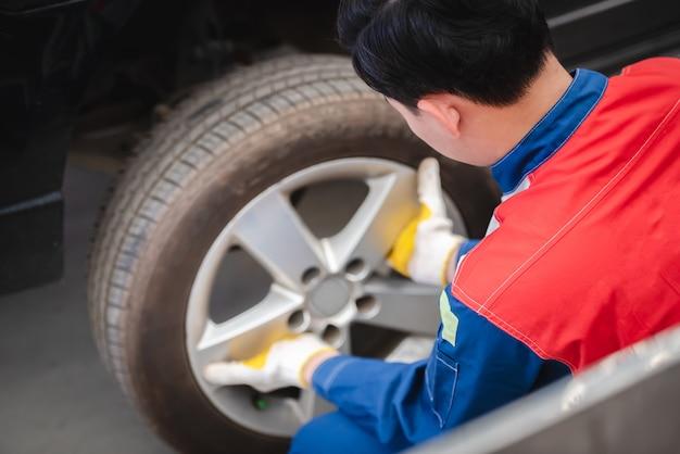 El mecánico de automóviles asiático está quitando la rueda y revisando los frenos y la suspensión en el servicio del automóvil con una carretilla elevadora. centro de reparacion y mantenimiento