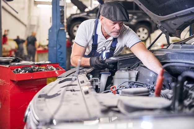 Mecánico de automóviles barbudo que fija el motor del coche en la estación de servicio