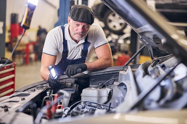 Mecánico de automóviles barbudo que trabaja en la estación de servicio de reparación de automóviles