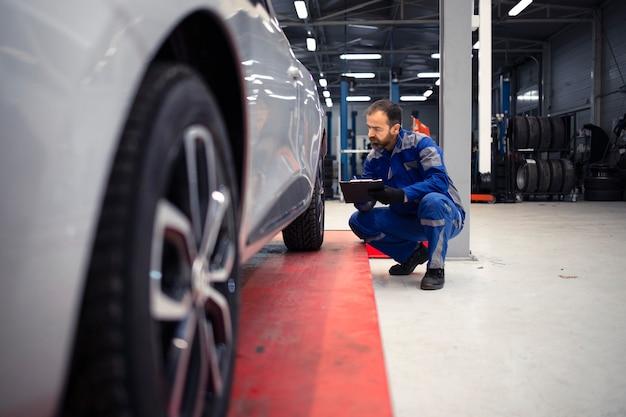 Mecánico de automóviles caucásico barbudo de mediana edad profesional haciendo inspección visual del vehículo en el taller y sosteniendo la lista de verificación.