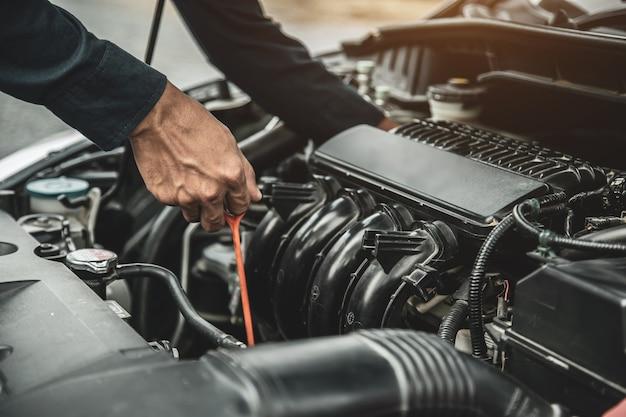 El mecánico de automóviles está comprobando el nivel de aceite del motor del vehículo