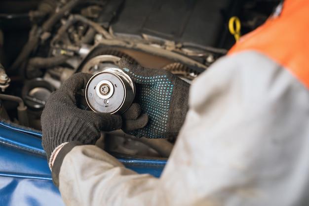 Un mecánico de automóviles comprueba el estado del rodillo tensor de la correa de distribución