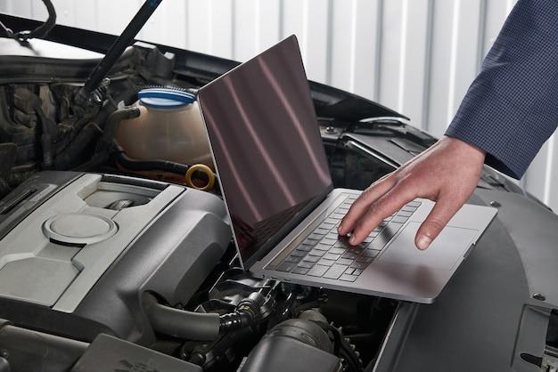 Mecánico de automóviles con computadora en taller de reparación de automóviles