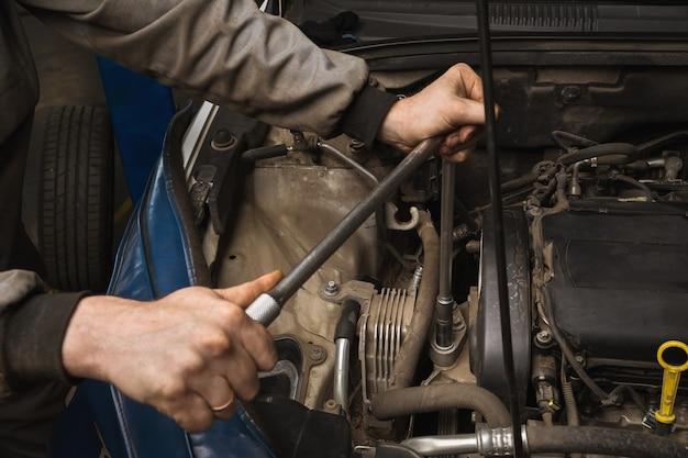Un mecánico de automóviles desenrosca el soporte del motor para reemplazar la correa de distribución