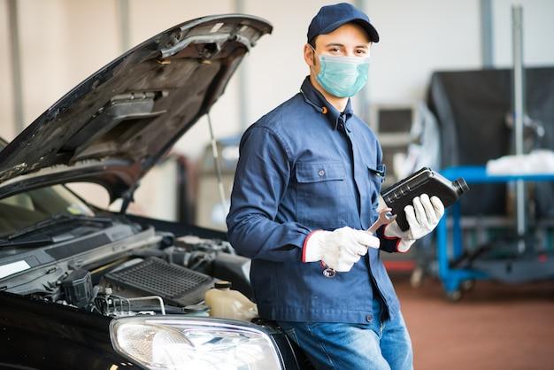 Mecánico de automóviles enmascarados sosteniendo una jarra de aceite de motor, concepto de trabajo de coronavirus