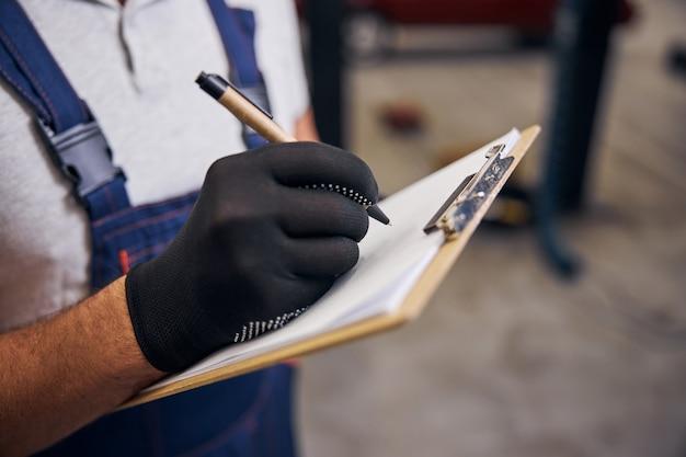 Mecánico de automóviles escribiendo en el portapapeles en la estación de servicio