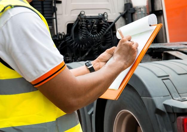 El mecánico de automóviles está escribiendo en el portapapeles con la inspección de un camión.
