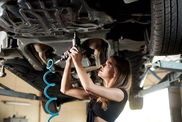 Mecánico de automóviles femenino repara el coche en el garaje