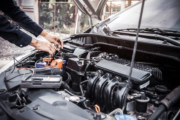 Mecánico de automóviles con herramienta de equipo de medición para comprobar la batería del coche.