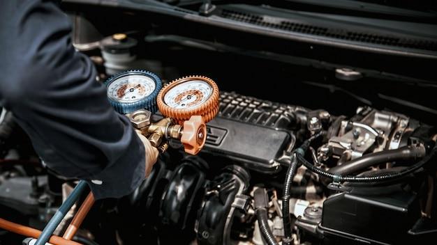 Mecánico de automóviles con herramienta de equipo de medición para el llenado de aire acondicionado de automóviles