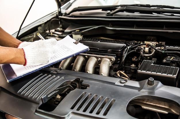 Mecánico de automóviles con lista de verificación para sistemas de motor de automóvil después de arreglar