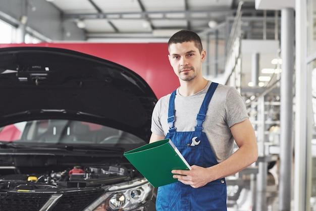Mecánico de automóviles o herrero con portapapeles en el taller.