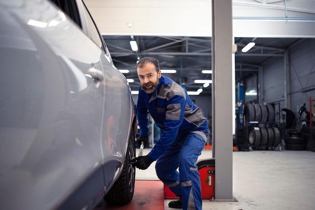 Mecánico de automóviles profesional que trabaja en el taller de vehículos y mantenimiento de automóviles.